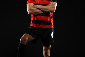 Soccer player with ball standing over black background