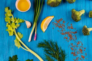 Parsley, fennel, celery, lemon and broccoli over blue wooden background