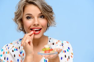 Portrait of young beautiful girl with sweets over blue background.