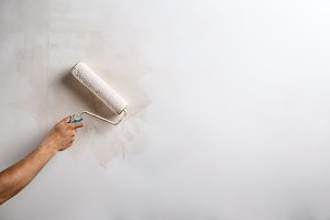 Close up of hand painting wall with roller. Copy space.