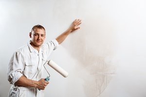 Worker looking at camera, holding roller. Copy space.