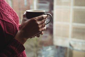Woman holding a coffee mug near the window
