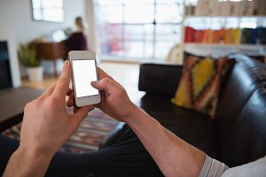 Hands of man using mobile phone in living room