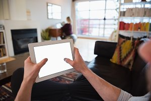 Close-up of man using digital tablet while relaxing on sofa in living room