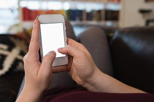Woman using mobile phone while relaxing on sofa in living room