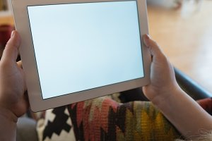 Woman using digital tablet while relaxing on sofa in living room