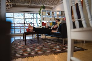 Couple reading books while relaxing in sofa in living room