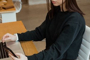 Female executive using mobile phone while working on laptop at desk
