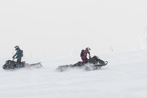 Couple riding snowmobile in snowy alps