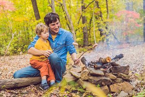 Happy father doing barbecue with his son on an autumn day