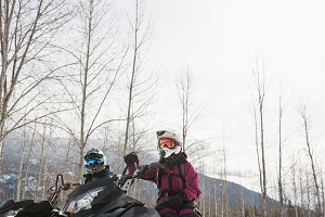 Couple relaxing on snowmobile in snowy alps