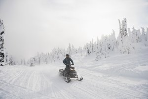 Man riding snowmobile in snowy alps