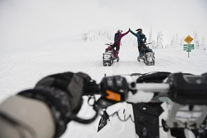 Couple giving high five to each other while riding snowmobile in snowy alps