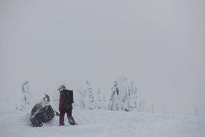 Man walking towards a fallen snowmobile