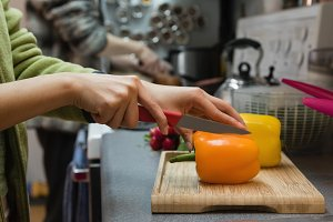 Mid section of woman cutting vegetables in kitchen