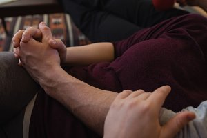 Affectionate couple holding hands while relaxing in living room