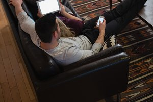 Couple using mobile phone and digital tablet on sofa in living room