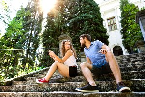 Young couple with smartphone sitting on stairs in town.