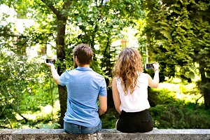 Young couple with smartphones sitting on concrete wall.