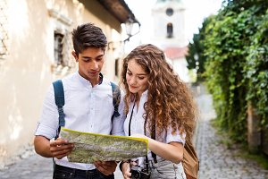 Two young tourists with map and camera in the old town