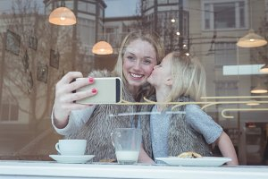 Mother and daughter taking a selfie on mobile phone