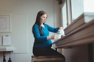 Pregnant woman having coffee in restaurant