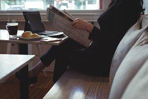 Woman reading newspaper in restaurant