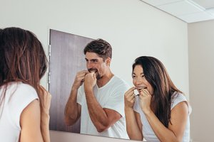 Couple using dental floss to clean