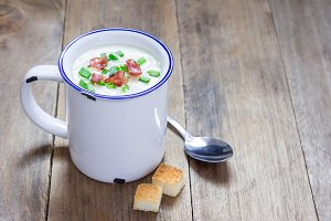 Creamy potato soup garnished with bacon and green onion, served in mug, copy space