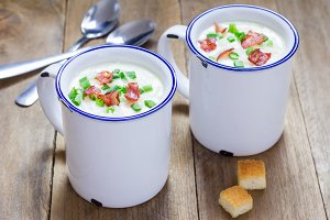 Creamy potato soup garnished with bacon and green onion, served in mug