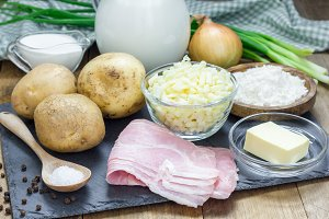 Ingredients for creamy potato soup garnished with bacon and green onion