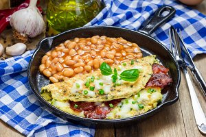 Bacon stuffed omelette with backed beans on a iron cast pan