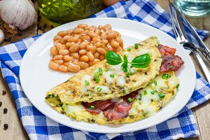 Bacon stuffed omelette with backed beans on a white plate