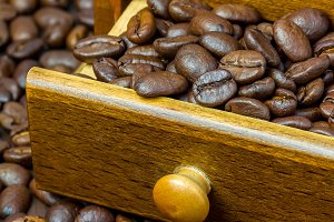 Fragrant coffee beans in coffee grinder, close up