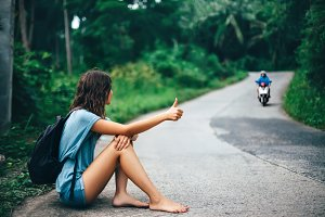 woman hitchhiking sitting on road