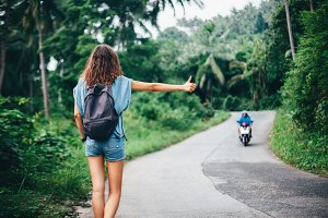 woman hitchhiking standing on road