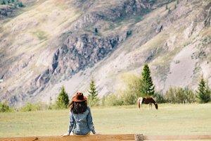 Девушка возле паддока с лошадьми