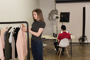 Young model choosing clothes with photographer sitting on chair