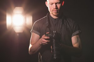 Male photographer holding camera