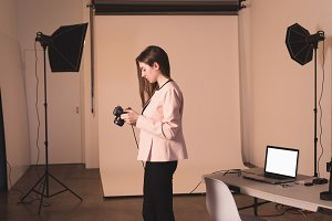 Side view of female model holding camera