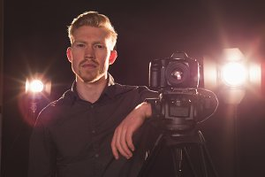 Portrait of photographer standing by camera