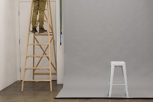 Low section of photographer on step ladder by backdrop