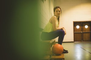 Side view portrait of female basketball player on bench
