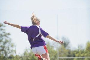 Rear view of woman kicking soccer ball