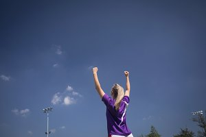Rear view of soccer player with arms raised