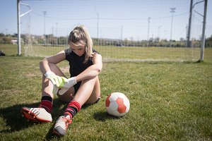 Female soccer player resting on field