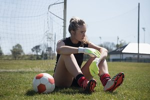 Female soccer player sitting on field