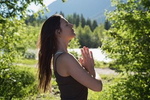 Woman doing prayer pose in forest