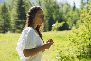 Beautiful woman blowing dandelion in park