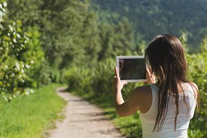 Woman using digital tablet in forest path